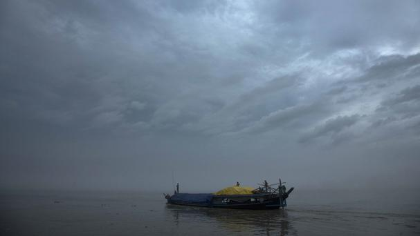 A boat carrying flood relief materials moves through the River Brahmaputra in north-eastern Assam state after torrential monsoon rains caused widespread flooding (AP)