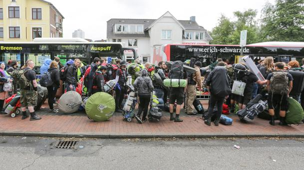Wacken Open Air festival-goers wait at the train station with their luggage to be transported to the festival grounds in Itzehoe, northern Germany (Axel Heimken/dpa via AP)