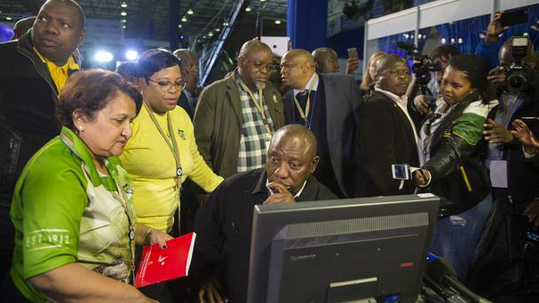Cyril Ramaphosa, seated, and African National Congress party members discuss the election results (AP)