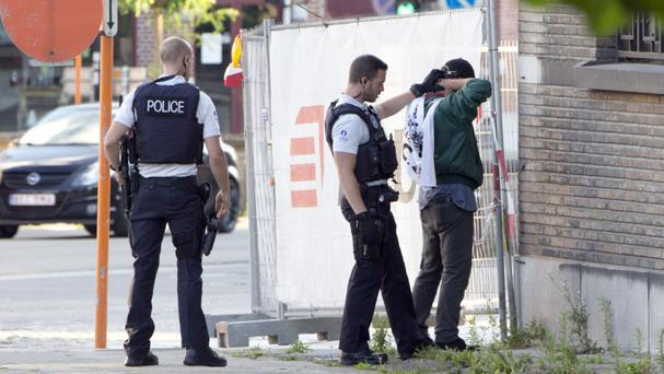 Police officers check the identification of a man near the police headquarters in Charleroi (AP)