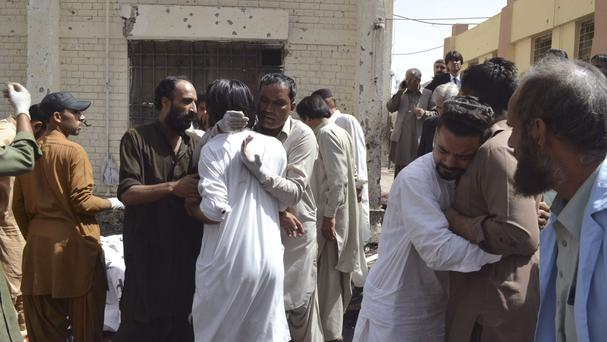People comfort each other following the bomb blast in Quetta, Pakistan (AP)