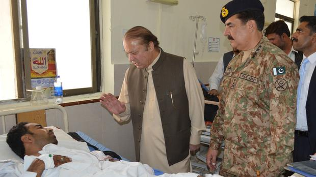 Pakistan's Prime Minister Nawaz Sharif talks to a survivor of the suicide bomb attack at a hospital in Quetta (AP)