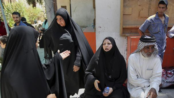 Families of newborn babies who died in a fire gather outside a maternity ward at Yarmouk hospital in western Baghdad (AP)