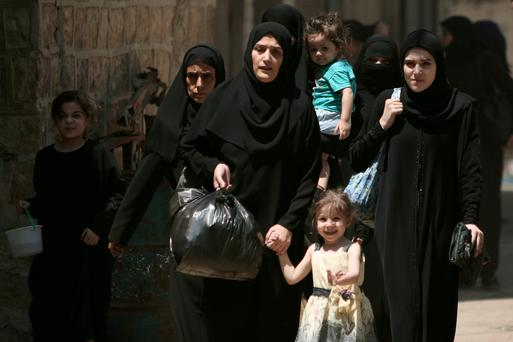 Women and children carry belongings as they flee towards safer parts of Manbij city, in Aleppo Governorate, Syria. Photo: Rodi Said/Reuters