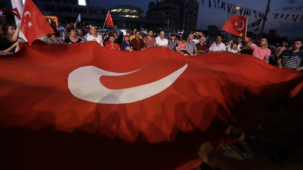 Supporters of Turkish President Recep Tayyip Erdogan wave a big flag following a failed coup (AP)