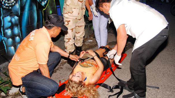 Rescue workers help a woman injured in one of the bomb blasts in Hua Hin (Daily News/AP)