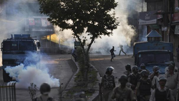 Kashmiri Muslim protesters run for cover from tear gas in Srinagar, Indian-controlled Kashmir (AP)