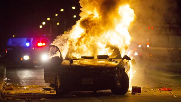A car burns as a crowd of more than 100 people gathered after the fatal shooting of a man in Milwaukee (Milwaukee Journal-Sentinel/AP)