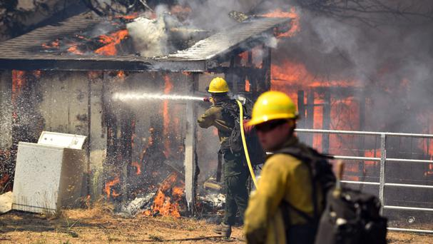 Firefighters battle flames as a house burns in Lower Lake, California (AP)