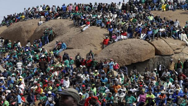 Mine workers sit on a hill during the commemoration near Marikana in Rustenburg, South Africa (AP)