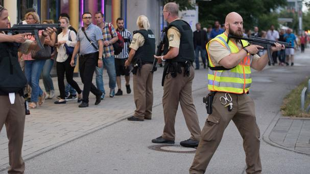 Police escort people leaving the Olympia shopping centre during the rampage in Munich (AP)
