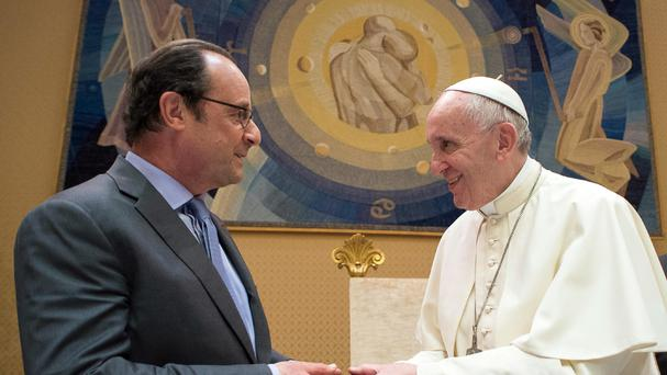 Pope Francis and French president Francois Hollande exchange gifts on the occasion of their private audience at the Vatican (L'Osservatore Romano/Pool Photo via AP)