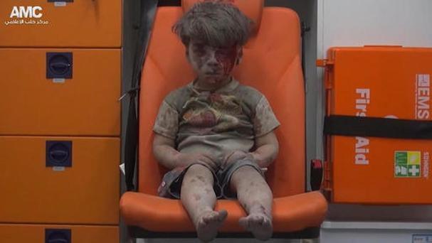 A child sits in an ambulance after being pulled out of a building hit by an air strike in Aleppo, Syria (Aleppo Media Centre via AP)