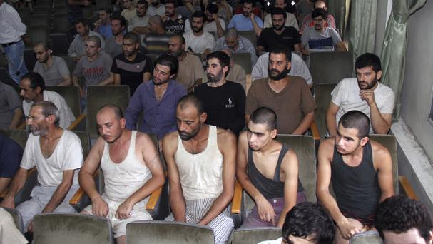 Syrian prisoners sit in a courtroom before their release in Damascus, in 2012 - a new report says 17,723 people have died in custody (AP)