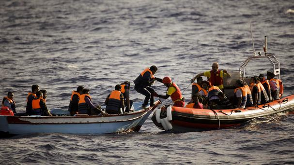 Migrants and refugees fleeing Libya are assisted by members of a Spanish NGO, during a rescue operation in the Mediterranean Sea (AP)