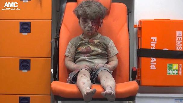 A child sits in an ambulance after being pulled out of a building in Aleppo, Syria (Aleppo Media Centre via AP)