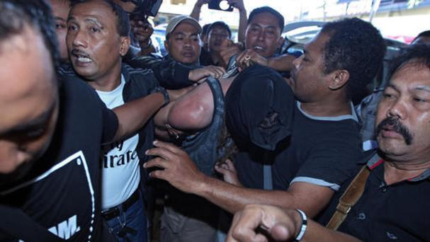 Indonesian police officers escort David Taylor, centre, as he covers his face at police headquarters in Bali, Indonesia (AP)