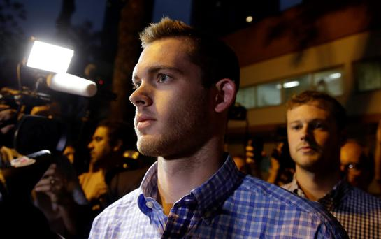 American Olympic swimmers Gunnar Bentz, front, and Jack Conger leave a police station in Rio Photo: AP