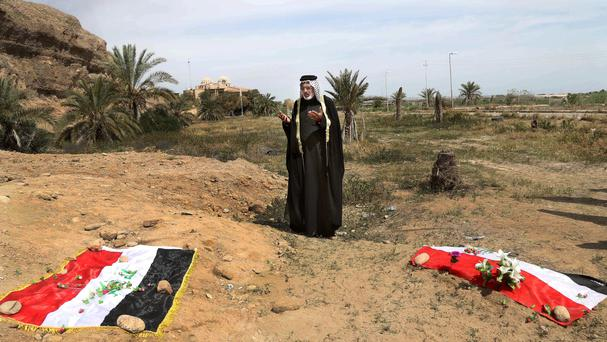 A man prays for his relative at the site of a mass grave believed to contain the bodies of Iraqi soldiers killed by IS militants (AP)