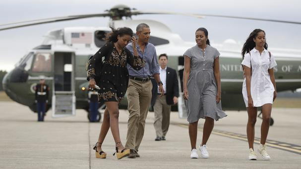 President Barack Obama with Michelle Obama and their daughters Malia, right, and Sasha, as they board Air Force One at Air Station Cape Cod (AP)