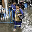 Women wade through a flooded street after heavy rain in Kolkata, eastern India (AP)