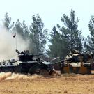 A Turkish army tank and an armoured vehicle are stationed near the border with Syria, in Karkamis, Turkey (IHA via AP)
