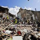 Rescuers search a crumbled building in Arcuata del Tronto, central Italy (AP)