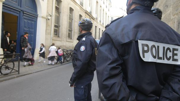 Schoolchildren leave a school in Paris watched by police officers. (AP)