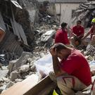 Rescuers pause in Amatrice, one of the towns hardest hit by the earthquake (AP)