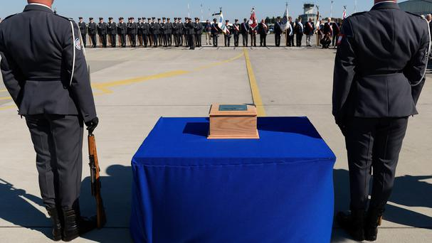 A wooden urn with the ashes of Polish fighter ace Captain Kazimierz Sporny is greeted with military honours at the Krzesiny Air Base in Poznan (AP)