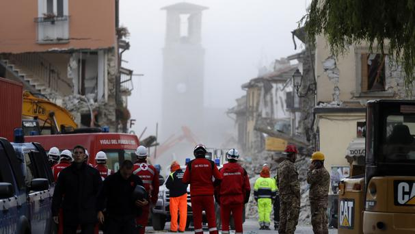 A bell tower is wrapped in a cloud of dust moments after an aftershock in Amatrice, central Italy (AP)