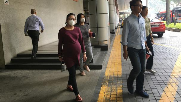 Office workers wear masks to protect themselves from the hazy weather in Singapore (AP)