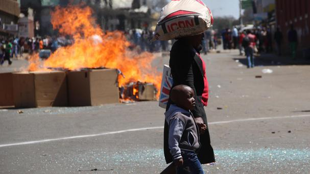 A woman and child pass a fire set alight during a protest in Harare (AP)