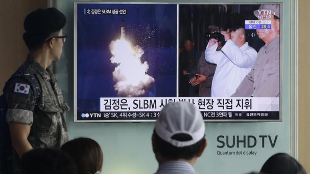 A TV news programme shows images published in North Korea's Rodong Sinmun newspaper of this week's ballistic missile launch and North Korean leader Kim Jong-un (AP)