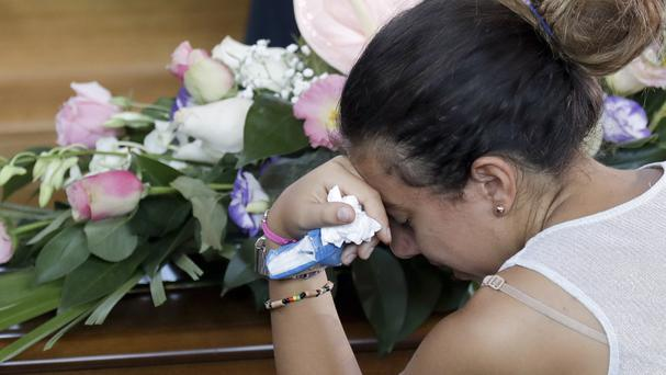 Relatives mourn their loved ones killed in the earthquake (AP)