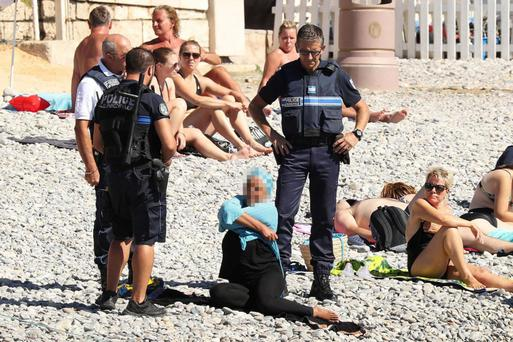 VISUAL AGE: The photo of a woman being asked to remove her burkini on a beach in Nice