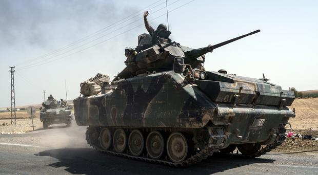 Turkish troops head to the Syrian border in Karkamis (AP)