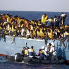 Italian officers rescue a woman from a crowded wooden boat carrying more than 700 migrants (AP Photo/Emilio Morenatti)