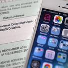 An Apple iPhone beside a tax return form as the tech giant faces a huge tax bill following an EU probe into its 'sweetheart deal' with the Irish Government