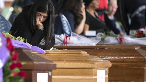 Mourners view a line of coffins at the state funeral for some of the victims of last week's earthquake in Amatrice (AP)