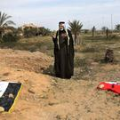A man prays for dead relatives at the site of a mass grave believed to contain the bodies of Iraqi soldiers killed by Islamic State militants (AP)