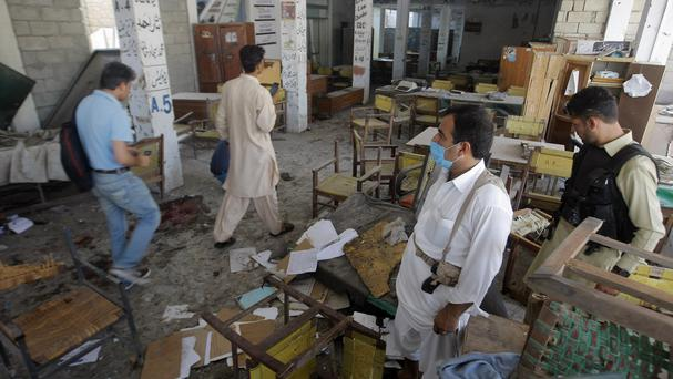Officials examine the site of bombing in Mardan, north-western Pakistan (AP)