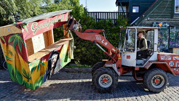 Residents of Christiania use a digger to remove illegal hashish stalls in Pusher Street (AP/POLFOTO)
