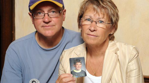 Patty and Jerry Wetterling pictured in 2009 show a photo of their son Jacob, who had been abducted in 1989 (AP)
