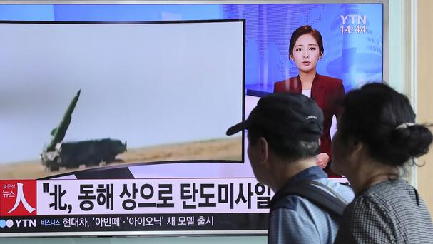 People in South Korea watch a TV news programme reporting about North Korea's missile launch (AP)