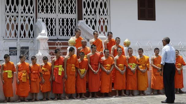 US President Barack Obama stands before temple monks as he tours the Wat Xieng Thong Buddhist Temple in Luang Prabang, Laos (AP)