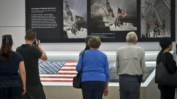 Visitors view the display for the American flag that firefighters hoisted at Ground Zero on 9/11 (AP)