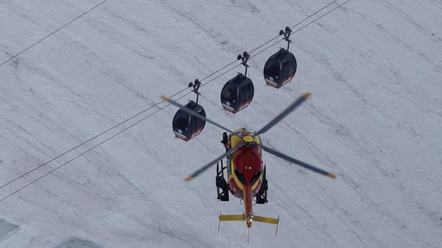 A rescue helicopter hovers over the Mont Blanc cable car (Luca Bruno/AP)