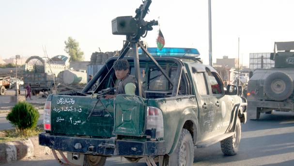 An Afghan policeman travels in the back of a truck in Tirin Kot, the capital of Uruzgan province southern of Kabul (AP)