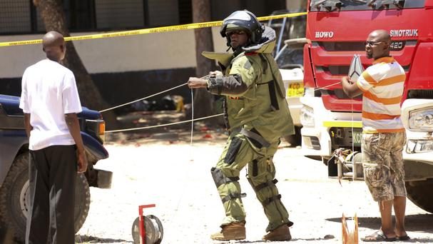 A member of a bomb disposal team prepares the scene outside the central police station in the coastal city of Mombasa, Kenya (AP)
